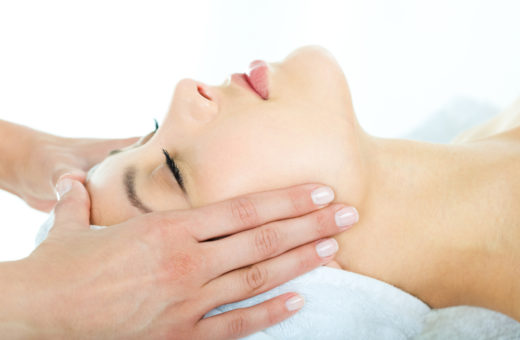 Photo of masseuse's hands doing relaxing massage on young woman's face